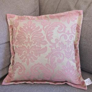 Kissen mit Ornamenten in rosa auf beigem Hintergrund im Innenbereich